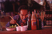 A Lao man eats with chopsticks in a restaurant with an open front in Vientiane