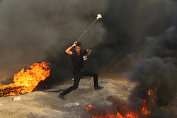 October 5, 2018 - Al-Buraj Refugee Camp, Gaza Strip - Palestinian protesters set fire to tires and throw rocks, while Israeli forces opened live fire and tear-gas bombs east of Al-Buraj refugee camp in central of the Gaza Strip, Two Palestinians killed and dozens wounded during 'Right of Return' clashes between Palestinians and Israeli troops. (Credit Image: © Hassan Jedi/Quds Net News via ZUMA Wire)