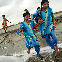 On Diwali Day, Krishnamurthy visits the beach with three of his daughters and a cousin close to their old home in Pudupettai. This is the first time the sisters had visited the beach since the tsunami. LtoR: Jayapriya, Bhanpriya and Sivaranjini.<br /><br />These photographs encompass four years in the lives of two families of children from South India who lost their mothers to the Asian tsunami. Following that momentous event in 2004, the five Krishnamurthy sisters from Puddupettai went to live in the Cuddalore Government Special Home for Tsunami Children. And Vijitha and Vijyashree Viswanathan, after an initial brief spell at the same home, now live with their father and his new wife in the nearby fishing village of Thalanguda. <br /><br />Each child affected by the tsunami had to adapt to changed circumstances and cope with emotions no one in their family could have possibly anticipated. The younger children seemed to adjust more quickly than their older siblings. And, while grief rendered some silent, in others it provoked a real sense of anger. Some became withdrawn while others craved attention and resorted to disruptive behavior. For all of the children, the experience of losing a parent seemed to strengthen the bond they shared with their brothers and sisters. <br /><br />The loss of a parent meant that some of the children photographed in this project inherited responsibilities that, while often a burden, provided a distraction from their own painful emotions. Sivaranjini Krishnamurthy lost her mother to the tsunami and then, together with her four younger sisters was abandoned by her father. At eleven years of age she took on the role of a mother to her younger sisters. Though she attends school and receives the support of orphanage staff, Sivaranjini has sacrificed much of her own childhood to take care of them. <br /><br />For Sivaranjini and the other children whose experiences are presented here, the tsunami is a defining event in their lives; the terri