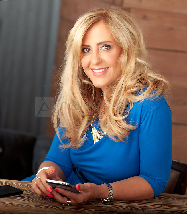 Relaxed corporate portrait featuring business woman taken in cool wine bar with raw wood panels holding IPHONE