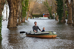 © Licensed to London News Pictures. 09/02/2014. Winchester, Hampshire, UK. A man and boy in their rubber dinghy on Park Avenue in Winchester. Water levels rose overnight in parts of the historic city where a flood warning has been issued by the Environment Agency for parts of the River Itchen. Photo credit : Rob Arnold/LNP