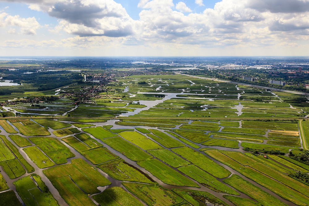 Nederland, Noord-Holland, Gemeente Oostzaan, 14-06-2012; polder Oostzaan, doorsneden door de spoorlijn Zaandam - Purmerend. Rechts autosnelweg A6 en Zaandam, links het lintdorp Oostzaan. De verkaveling in het gebied is het resultaat van veenontginning. .Polder and village Oostzaan, north of Amsterdam (at the horizon). The division in plots in the area is the result of peat extraction..luchtfoto (toeslag), aerial photo (additional fee required);.copyright foto/photo Siebe Swart