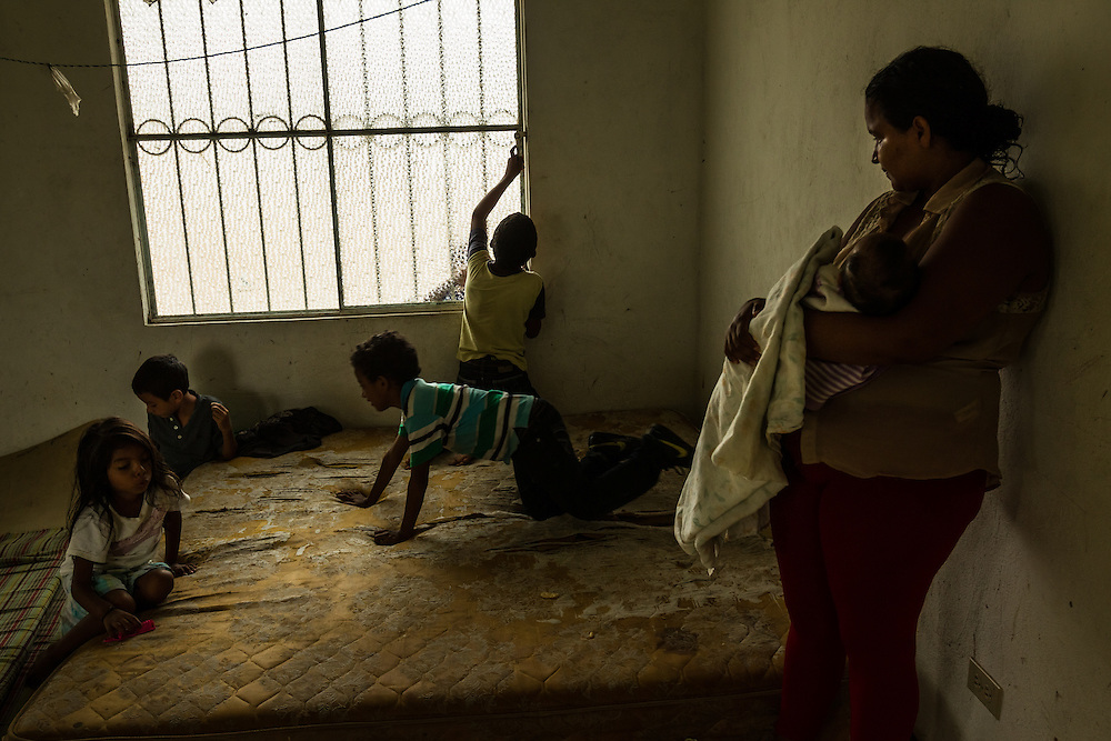 TENOSIQUE, MEXICO - JULY 2, 2014: Ruth Maribel Flores, 28, breastfeeds her 2-month old daughter, Genesis Gonzalez while other children play on a worn mattress at the 72 Migrant Shelter. Flores said her family was given an hour to surrender their home in Tegucigalpa under threat of death by gang members, who suspected her 9-year-old son was a lookout for a rival faction. He, too, is traveling with her along with her husband, Carlos Gonzalez, and they plan to work with shelter volunteers to seek a Mexican visa to allow them to say at least temporarily. She had to leave two of her other children in Honduras with family members, and said through tears that it was the hardes thing that she had ever had to do in her life. PHOTO: Meridith Kohut for The New York Times
