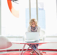 Businesswoman using laptop in creative office