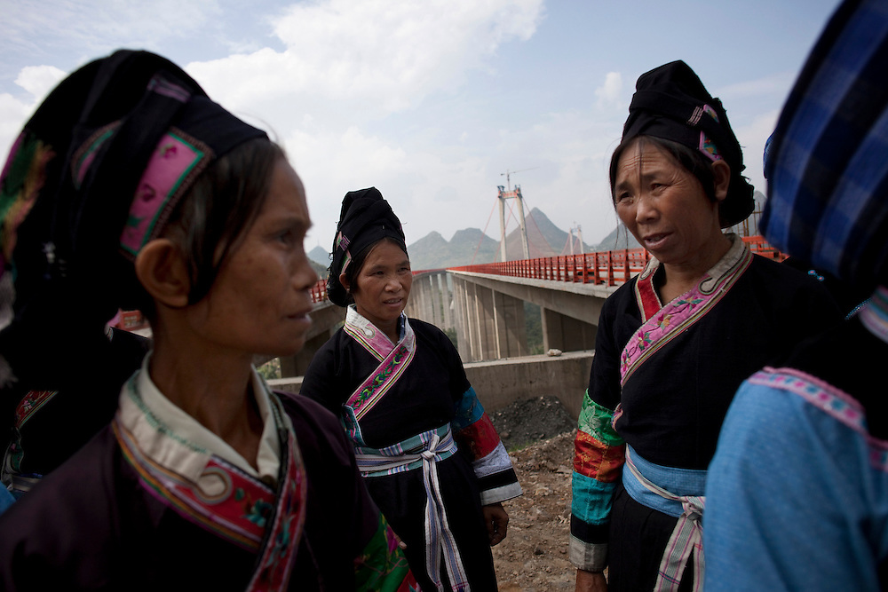 There is no word for tunnel in the Buyi language. Lu Deqing calls it &ldquo;the long cave.&rdquo; Lu, at left, is dressed in her finest as she and the other village ladies visit the entrance where the tunnel meets the bridge platform. They are proud of the bridge and the fact that it spans over their valley. They sing songs praising its beauty and hope the bridge will bring some good to their lives. <br /> <br /> Private investors have already contacted bridge engineer Zhou. They want to invest 70 to 80 million yuan to develop the Baling River valley. Their plans include building a luxury hotel, theme park and a glass restaurant with river views. Activities will include paragliding and bungee jumping. Tourists will want to see the local minorities and have them sing and dance for their entertainment, wearing satin and sequined parodies of their traditional clothing.