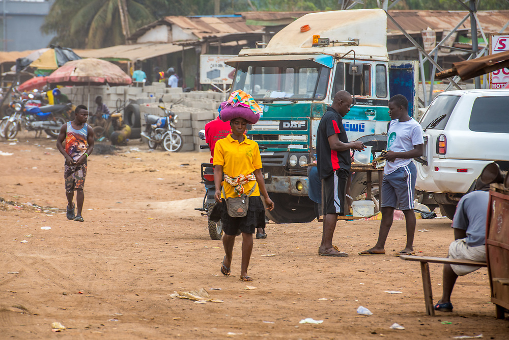 A woman carries a bundle on her head through Ganta Liberia