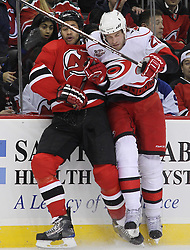 Feb 16; Newark, NJ, USA; Carolina Hurricanes right wing Troy Bodie (20) hits New Jersey Devils defenseman Mark Fraser (2) during the first period at the Prudential Center.