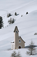 A modern style chapel on a snow covered hillside at Passo Sella in the Dolmites Mountains, South Tyrol, Italy