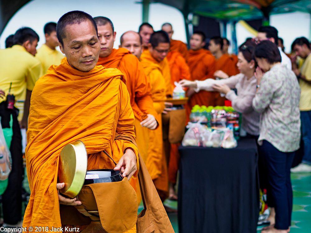 26 JULY 2018 - BANGKOK, THAILAND:  Buddhist monks collect donations from office and retail workers from neighboring malls during a merit making ceremony in the Pathumwan area of Bangkok to honor Thai King His Majesty King Maha Vajiralongkorn Bodindradebayavarangkun, also known as Rama X, for his 66th birthday. The King's birthday is 28 July, and events are scheduled throughout Thailand to honor His Majesty. The Pathumwan merit making was organized by businesses in the area.       PHOTO BY JACK KURTZ