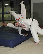"Vince Ashcraft, from Piqua (face visible) trains with Joe Sherman, from Covington during a judo class in the Miami County YMCA, Thursday, May 31st. They use these 'crash mats' to practice full force throws.  Ashcraft says the landing is, ""like a featherbed."""