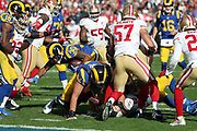 Players look on as Los Angeles Rams running back Todd Gurley (30) dives for the goal line while running for a 1 yard touchdown that ties the first quarter score at 7-7 during the 2016 NFL week 16 regular season football game against the San Francisco 49ers on Saturday, Dec. 24, 2016 in Los Angeles. The 49ers won the game 22-21. (©Paul Anthony Spinelli)