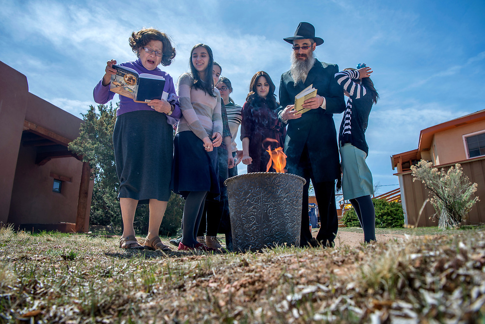 em041017b/metro/From left, Bracha Levertov, her grandaughters Sara, 15, Ester, 17, Rivka, 18, Mussi, 20, her son Rabbi Berel Levertov, and grandaughter Cirel, 10, read a prayer while burning of the chametz outside their home in Santa Fe, Monday April 10, 2017. On Passover they go through their home and collect anything levain and clean all surfaces and burn them before noon. Rabbi Levertov said it's to burn away our egos, to become humble, fresh, to rebuild a healthy self. (Eddie Moore/Albuquerque Journal