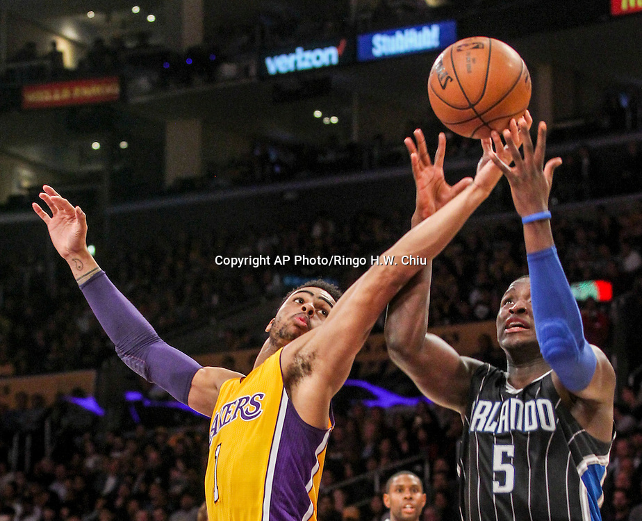 Los Angeles Lakers guard D'Angelo Russell, left, and Orlando Magic guard Victor Oladipo battle for a ball during the second half of an NBA basketball game Tuesday, March 8, 2016, in Los Angeles.  Lakers won 107-98. (AP Photo/Ringo H.W. Chiu)