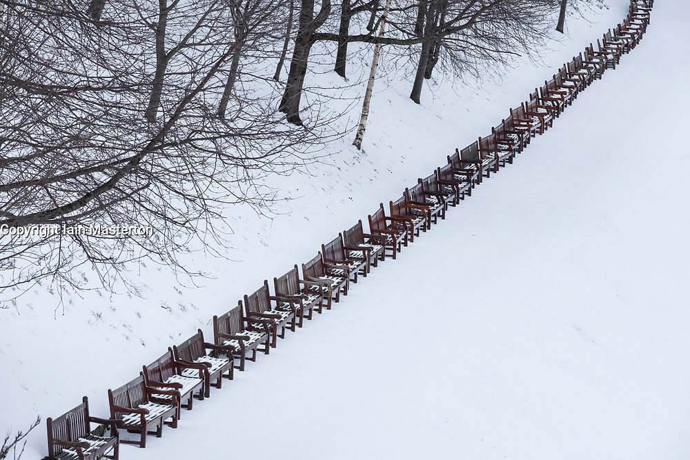 Row of empty park benches in Princes Street Gardens in Edinburgh covered in thick snow after heavy snow storms, Scotland, United kingdom