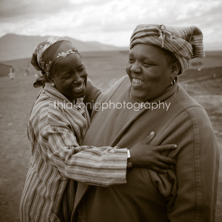 Two black woman hug with big smiles - one is much larger than the other's arm span - at a crossroads in Losotho, Africa.