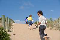 Three pre-teen boys running towards beach