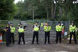 © licensed to London News Pictures. London, UK 03/08/2013. Police officers and G4S security guards guarding the entrance of Cuadrilla's drilling site in Belcombe. A protest against oil exploration in Balcombe, West Sussex enters its 10th day on Saturday, August 03, 2013, a day after energy company Cuadrilla began drilling at the site. Photo credit: Tolga Akmen/LNP