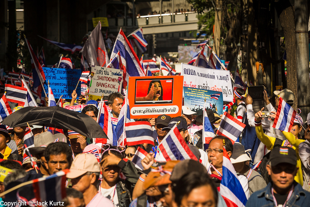 "15 JANUARY 2014 - BANGKOK, THAILAND:  Anti-government protestors follow Suthep Thaugsuban up Sukhumvit Road during a protest march in Bangkok Wednesday. Tens of thousands of Thai anti-government protestors continued to block the streets of Bangkok Wednesday to shut down the Thai capitol. The protest, ""Shutdown Bangkok,"" is expected to last at least a week. Shutdown Bangkok is organized by People's Democratic Reform Committee (PRDC). It's a continuation of protests that started in early November. There have been shootings almost every night at different protests sites around Bangkok. The malls in Bangkok are still open but many other businesses are closed and mass transit is swamped with both protestors and people who had to use mass transit because the roads were blocked.   PHOTO BY JACK KURTZ"