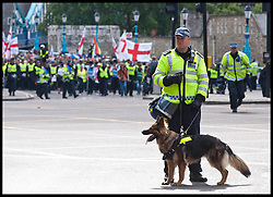 A policeman holds a police dog during an EDL protest against what the EDL sees as the influence of Islam in the Tower Hamlets area of London, United Kingdom. Saturday, 7th September 2013. Picture by Piero Cruciatti / i-Images