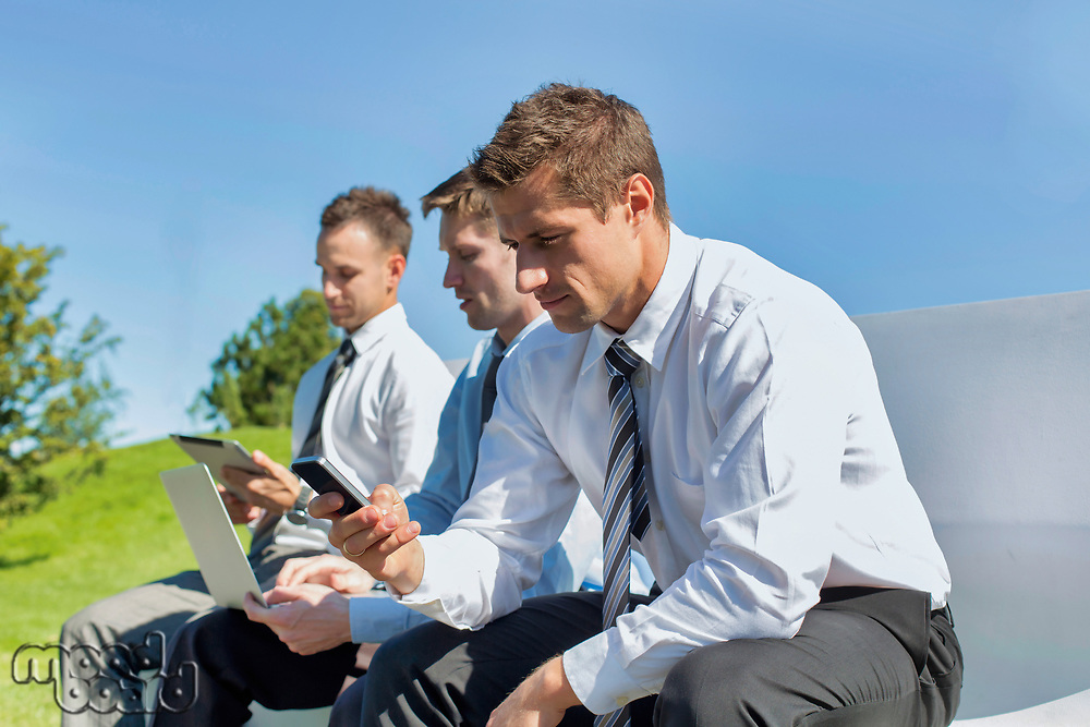 Group of mature businessmen sitting on bench while using gadgets