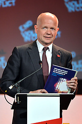 Image ©Licensed to i-Images Picture Agency. 11/06/2014.<br /> <br /> William Hague holds up the International Protocol on the Documentation and Investigation of Sexual Violence in Conflict as he speaks at the Global Summit to End Sexual Violence in Conflict at The ExCel, London, UK.<br /> <br /> Picture by Ben Stevens / i-Images