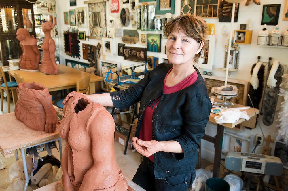 Nederland, Den Bosch, 20080909..Kunstenares Marlies Krijgsman op haar atelier.  Is een beeld van klei aan het opbouwen..