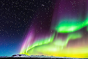 A solar storm peaks with a brilliant display of Northern Lights at Thingvellir National Park in Iceland. The aurora's rare purples and reds illuminated the night sky.