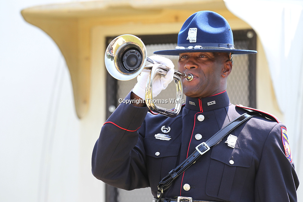 Mississippi Highway Patrolman larry Edwards plays taps following the 21 gun salute to conclude Wednesday's service.