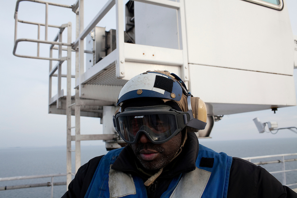 A man waits for a helicopter to land on the flight deck of the USNS Comfort, a naval hospital ship, as it makes its way to Haiti to help earthquake survivors on Saturday, January 16, 2010 in the Chesapeake Bay.