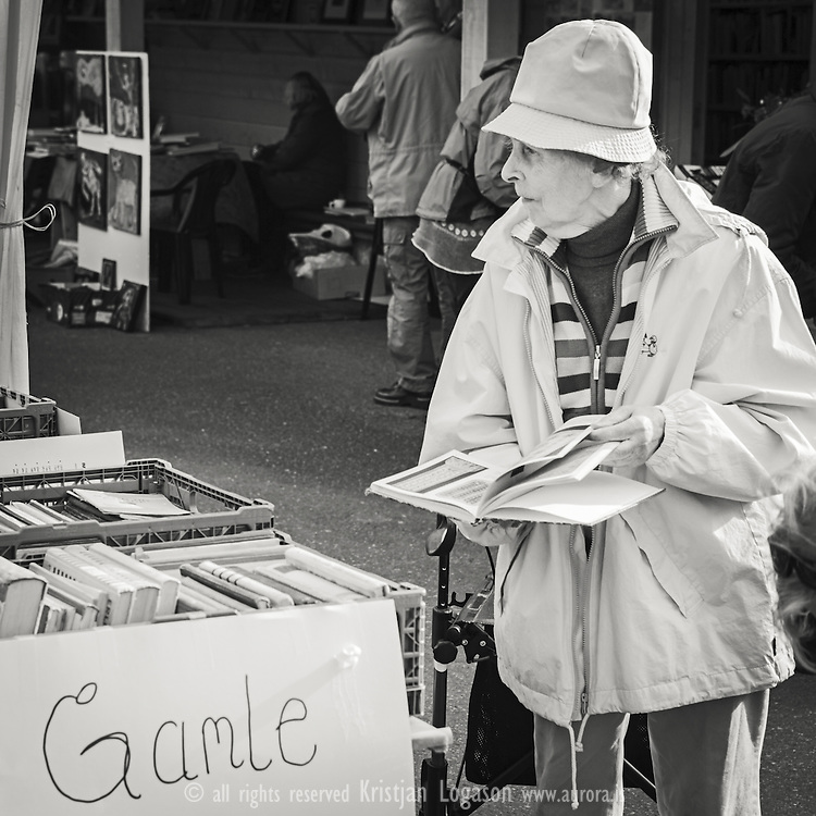 Elderly woman standing by a table filled with books and a sign that says Old at the bokk night in the book town of Fjærland Sogn og fjordane Norway