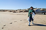14 FEBRUARY 2003 -- PUERTO PENASCO, SONORA, MEXICO: Maria Francesca Luna Javalera, a member of an oyster growing co-operative, walks down to the water to  harvest oysters near Puerto Penasco, Sonora, Mexico. Puerto Penasco is known as Rocky Point among visitors to the Mexican beach town on the Sea of Cortez. The area is famous for wide beaches and fresh seafood, especially shellfish.     PHOTO BY JACK KURTZ