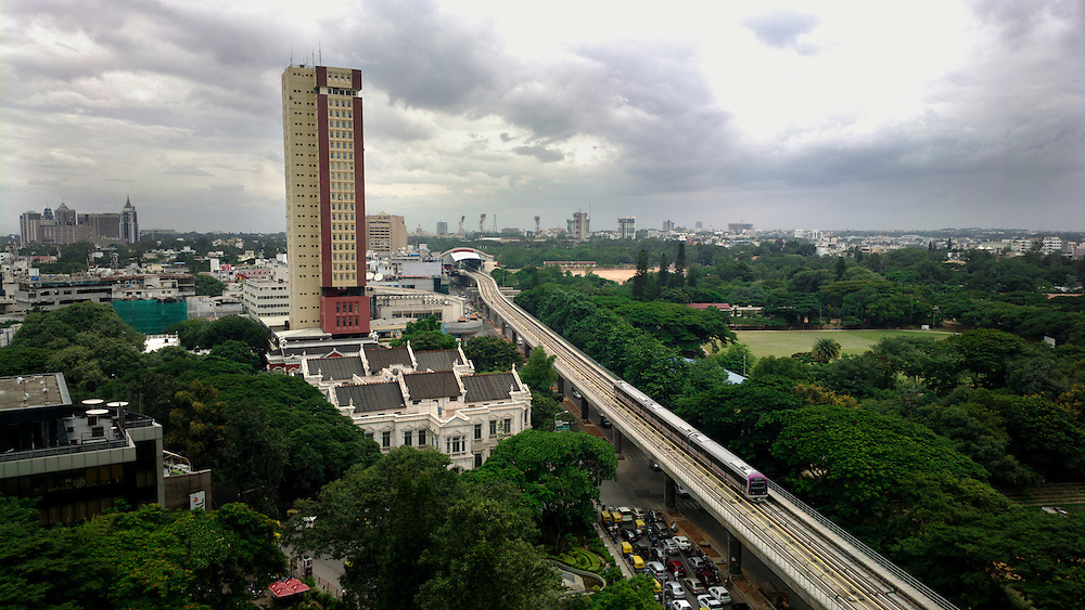 An aerial view of the metro line on MG Road, Bangalore. The white building in the foreground is Mayo Hall, built in the late 19th century.