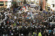 Anti-war protestors march down Clark Street in  downtown Chicago Saturday afternoon contained by thousands of police dressed in riot gear.  The protest was to mark the first anniversary of the war in Iraq.