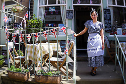 © Paul Thompson licensed to London News Pictures. 15/05/2015. Haworth, West Yorkshire, UK. A waitress at The Cookhouse, a Haworth cafe, in 1940s dress for the 1940s weekend. The 1940s weekend is an annual event in which people dress in period costume and visit the village of Haworth to relive the 1940s. Photo credit : Paul Thompson/LNP