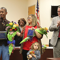 Aberdeen School District Teacher of the Year Micah Burnett of Belle-Shivers Middle School, left, is congratulated by Aberdeen Elementary School Teacher of the Year Erin Walker, as school board member Sandra Peoples and district superintendent Jeff Clay applaud him.