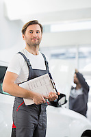 Portrait of confident male automobile mechanic with clipboard in car repair store