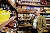 Small tobacco store owner looking at cigar boxes on display in shop