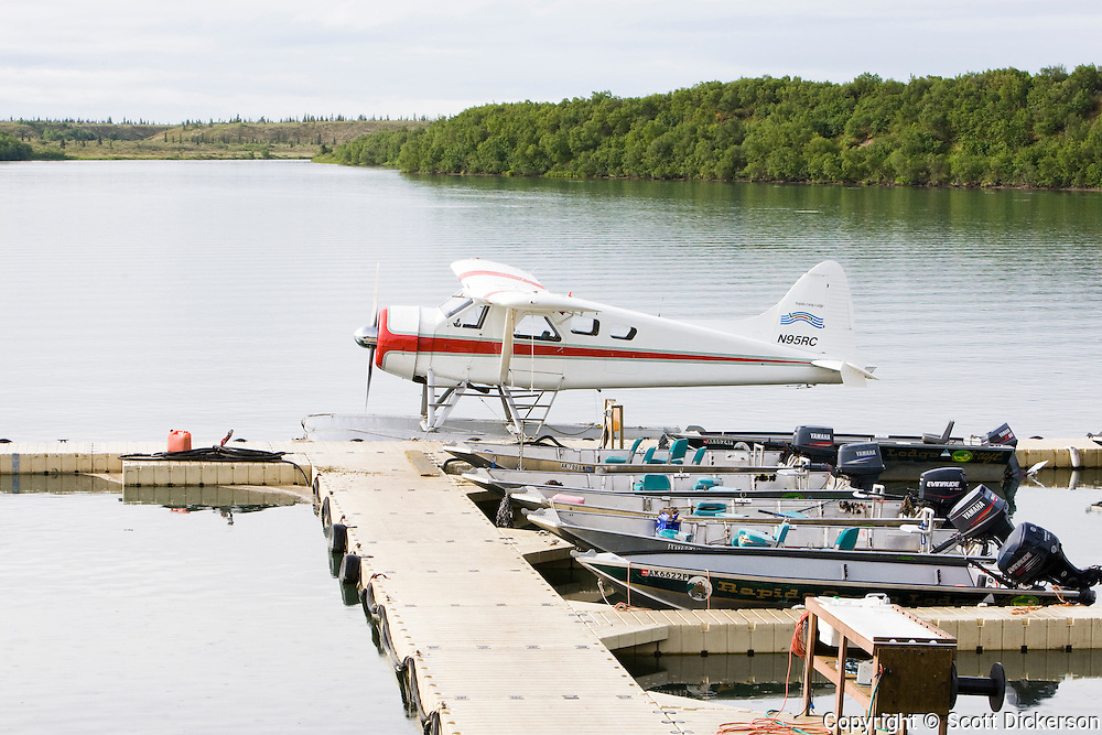Float plane and skiffs docked at Rapids Camp Lodge, a sport fishing lodge on the Naknek river in Bristol Bay, Alaska.