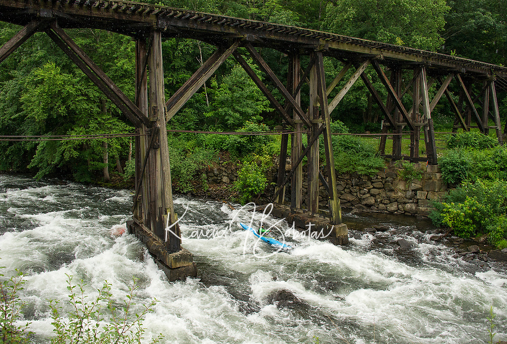 "A kayaker navigates the trestle during ""Winni River Days"" whitewater festival in Franklin on Saturday.  (Karen Bobotas/for the Laconia Daily Sun)"