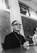 Children peer down from a window above as Archbishop Oscar Romero of El Salvador speaks about human rights abuses by the government of El Salvador after saying Mass in his Church of the Divine Providence in San Salvador, El Salvador where he was later slain at the alter by a right wing gunman in 1980. Óscar Arnulfo Romero y Galdámez was a bishop of the Catholic Church in El Salvador. He became the fourth Archbishop of San Salvador, succeeding Luis Chávez, and spoke out against poverty, social injustice, assassinations and torture. Romero was assassinated while offering Mass on March 24,1980. - To license this image, click on the shopping cart below -