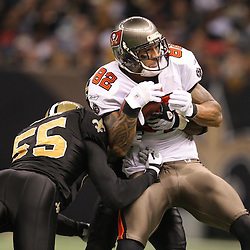 Dec 27, 2009; New Orleans, LA, USA;  Tampa Bay Buccaneers tight end Kellen Winslow (82) is tackled by New Orleans Saints linebacker Scott Fujita (55) and cornerback Tracy Porter (rear) during the second quarter at the Louisiana Superdome. Mandatory Credit: Derick E. Hingle-US PRESSWIRE..