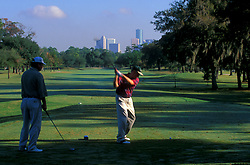 Stock photo of two golfers at Hermann Park Golf Park with the downtown Houston skyline in the background