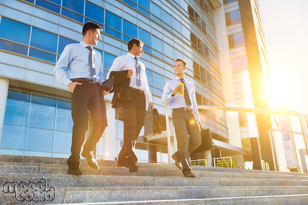 Mature businessmen talking while walking downstairs against office building after work