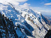 Dôme du Goûter (center 14,121 feet or 4304 meters) is a shoulder of massive Mont Blanc (in clouds on left at 15,782 feet elevation). Massive glaciers fill the view from Aiguille du Midi, Chamonix, France, Europe.