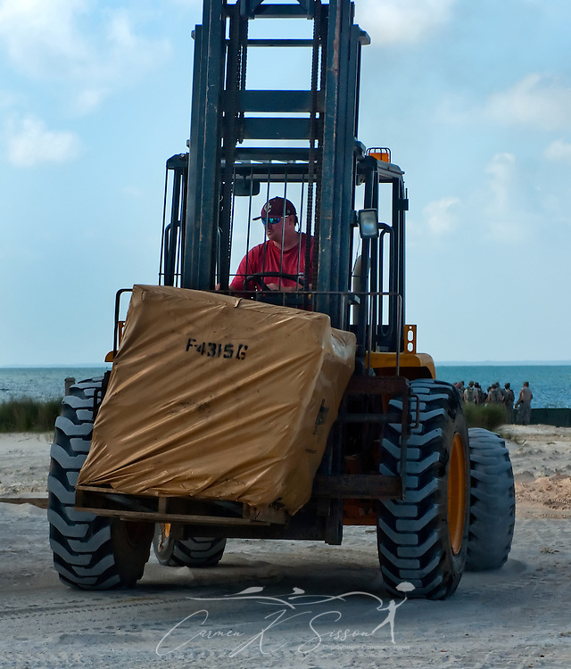 A MAECO equipment operator moves stacks of HESCO barriers on the west end of Dauphin Island, Alabama, where efforts to protect the island from oil threatening as a result of the Deepwater Horizon rig explosion earlier in the month were heavily underway May 7, 2010. The National Guard spent most of the day installing nearly four miles of HESCO barriers and filling the felt-like boxes with sand chemically treated to transform the oil into a solid which can then be safely removed. (Photo by Carmen K. Sisson/Cloudybright)