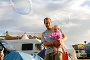 A man and a baby playing with bubbles, Boomtown, Matterley Estate, Alresford Road, near Winchester, Hampshire, UK, August, 2010