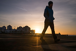 © Licensed to London News Pictures. 30/10/2017. Southsea, UK.  A woman walking along Southsea promenade as dawn breaks on a chilly autumn morning, 30th October 2017.  Photo credit: Rob Arnold/LNP