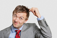 Young businessman pulling hair over colored background
