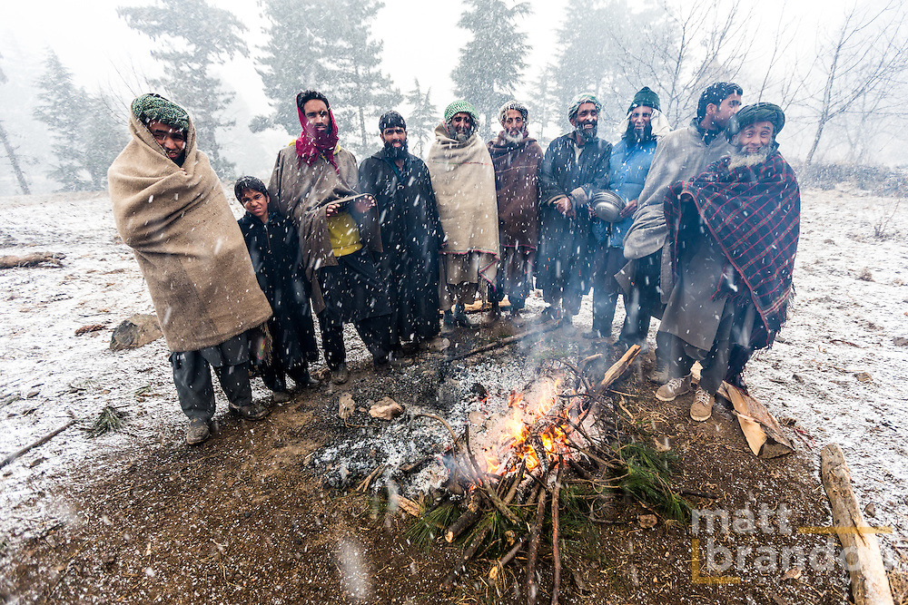 These Gujjars stay close to the fire to stay warm during perperations for a wedding meal. Pahalgam, Kashmir, India
