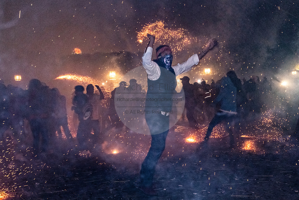 A Mexican man wearing a protective mask dances during a barrage of sky rockets during the Alborada festival September 29, 2018 in San Miguel de Allende, Mexico. The unusual festival celebrates the cities patron saint with a two hour-long firework battle at 4am representing the struggle between Saint Michael and Lucifer.